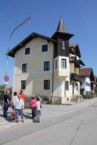 Der Ortsspaziergang hält bei einem Haus der Gemeinde
